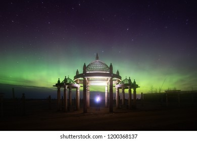 Yakutsk, Yakutia, Russia-October 08 2018: a man with a flashlight standing under the national traditional construction of the Yakuts and looking at the northern lights