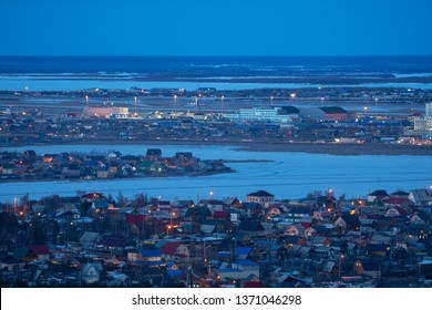 Yakutsk, Yakutia/Russia-April 14 2019: Aerial view of Yakutsk skyline with Beloe lake in beautiful post sunset twilight during blue hour at dusk with clear blue sky in cold spring