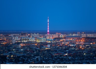 Yakutsk, Yakutia/Russia-April 14 2019: Aerial view of Yakutsk skyline with TV tower illuminated in bright colors and center of city in beautiful post sunset twilight during blue hour