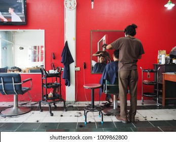 Yala Thailand. January 18-2018:Barber cutting hair for man front of mirror in barber shop
