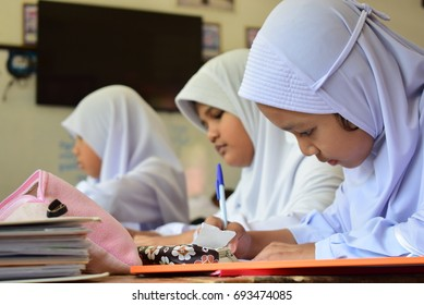 YALA THAILAND-September 21: There are 3 female students whose names are unknown. Writing in a notebook on the table and having several books in front.on September 21,2016 in Yala Thailand.
