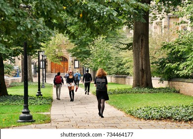 YALE UNIVERSITY, NEW HAVEN, CONNECTICUT, USA - OCTOBER 2017: Students walking on a path through old campus at Yale. Green trees surround the old brick buildings and a doorway can be seen beyond