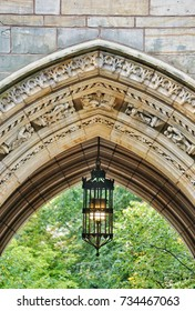 YALE UNIVERSITY, NEW HAVEN, CONNECTICUT, USA - OCTOBER 2017: A decorative stone archway at the entrance to a student college. An ornate light hangs in the archway. Green trees can be seen
