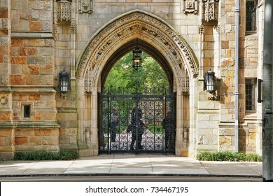 YALE UNIVERSITY, NEW HAVEN, CONNECTICUT, USA - OCTOBER 2017: A decorative stone archway at the entrance to a student college. An ornate metal gate is closed to prevent access. Green trees can be seen