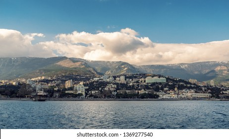 Yalta city panorama, view from water. Crimean resort on Black Sea, beautiful town at foot of mountains