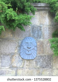 Yalta, Crimea / August, 2018: Relief on the wall of the Nikitsky Botanical garden in the form of a bearded head with a hole for the fountain