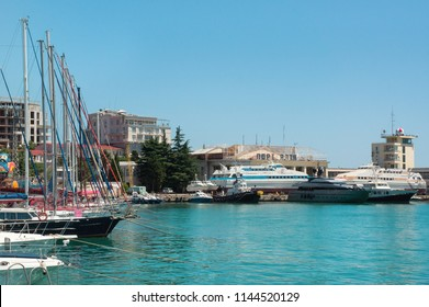 "YALTA, CRIMEA - June 20, 2018: Commercial seaport of Yalta, Crimea. Yachts and ships on Black Sea. Translation of the inscription on the port building: ""The Sea port of Yalta""."