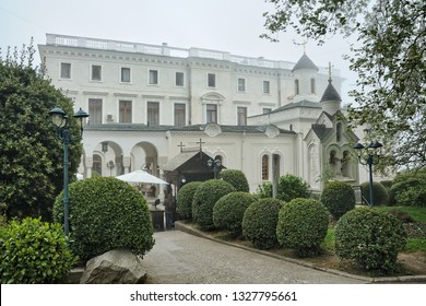YALTA, CRIMEA - May 05, 2017 View from Livadia park on the home church of Romanov's family with a small old style belfry at the side of the roayl palace framed by trees in a foggy spring day.