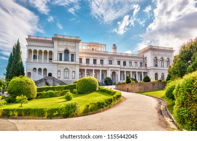 Yalta, Crimea - May 17, 2016: Livadia Palace with a beautiful landscaped garden in Crimea, Russia. Scenic view of a famous landmark of Crimea in summer. Historical architecture and nature of Crimea.
