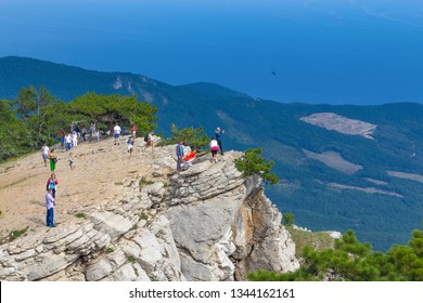 Yalta, Crimea - September 13, 2012: Tourists on the edge of the cliff Ai-Petri are admired and photographed against the backdrop of a beautiful landscape.