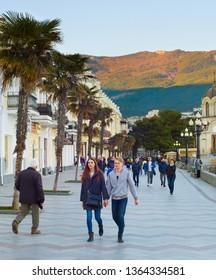YALTA, CRIMEA, UKRAINE - APRIL 03, 2018: Couple walking by Yalta promenade at sunset. Yalta is the most famous tourist destination in Crimea