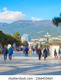 YALTA, CRIMEA, UKRAINE - APRIL 03, 2018: People walking by Yalta promenade in sunny day. Yalta is the most famous tourist destination in Crimea