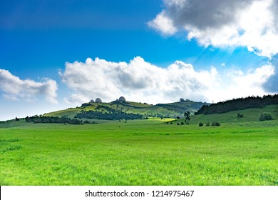 Yalta, Crimea-June 1, 2016: Natural landscape with a green field covered with grass under the blue sky with clouds.