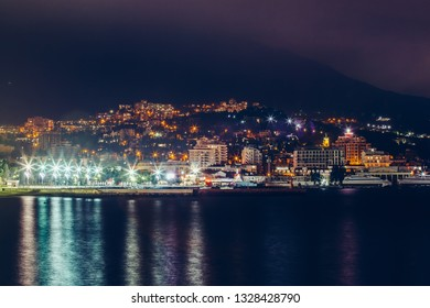 Yalta embankment at night, city buildings lights reflected in black water, beautiful resort in Crimea with mountains and sea, toned