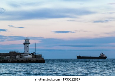 Yalta lighthouse against the backdrop of the rolling sea and evening twilight.