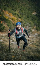 "Yalta, Russia - November 2, 2015: girl athlete with walking sticks going uphill during Mountain marathon ""Vertical kilometre AI-Petri"""