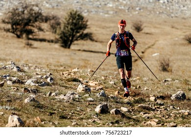 Yalta, Russia - October 11, 2017: male athlete runner with trekking poles runnning on mountain trail during marathon CrimeaXRun