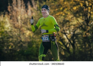 Yalta, Russia - October 31, 2015: middle-aged man athlete running autumn forest in compression clothing during First Yalta mountain marathon