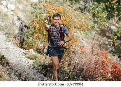 Yalta, Russia - October 5, 2016: male runner skyrunner runs on a mountain trail shows thumb up during Crimea mountain marathon