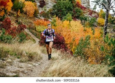 Yalta, Russia - October 5, 2016: runner skyrunner runs with walking sticks on a mountain trail in autumn forest during Crimea mountain marathon