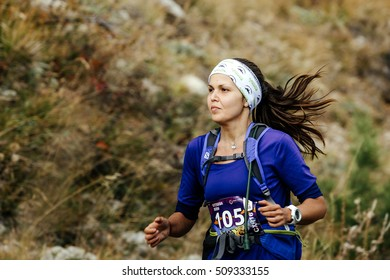 Yalta, Russia - October 5, 2016: closeup of young female runner skyrunner running mountain landscape during Crimea mountain marathon