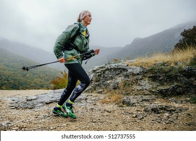 Yalta, Russia - October 8, 2016: runner middle-aged woman running in rain on a mountain trail with walking poles during Crimea mountain marathon