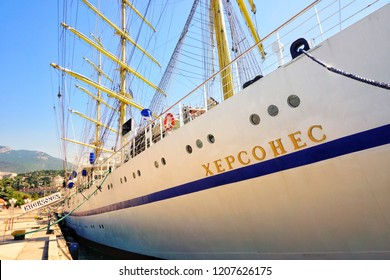 """YALTA- RUSSIA-AUGUST 2018. Tallship """"Chersonese"""" with three high masts, yards, ropes and name on white board."""