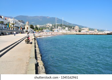 Yalta, Ukraine, May 2011. View on a promenade along seaside and Yalta city and mountains in the background.