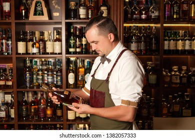 YALTA, UKRAINE, SEPTEMBER 06, 2017:  Barman with a bottle of brandy at the bar