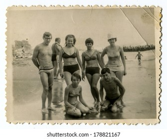 """YALTA, USSR - CIRCA 1960s : An antique photo shows group of people wading in the ocean . """"Soviet people"""" series."""