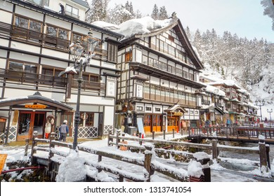 Yamagata, Japan - January 28, 2019 ; Winter view of Ginzan Onsen a famous Japanese hot spring town in Obanazawa, Yamagata, Japan, with bridges over stream flanked by antique wooden building of Ryokan.