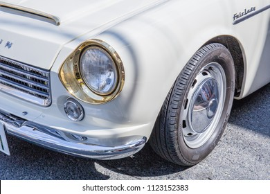 YAMAGUCHI, JAPAN - APRIL 8, 2018: A close up of the distinctive shiny gold headlight and chrome bumper of a vintage, classic, cream colored, Nissan Datsun Fairlady sports car.