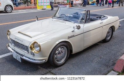 YAMAGUCHI, JAPAN - APRIL 8, 2018: A side angle view of a classic, cream colored, Nissan Datsun Fairlady convertible sports car with distinctive shiny gold headlights and a chrome bumper on a street.