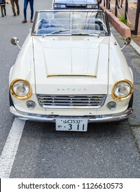 YAMAGUCHI, JAPAN - APRIL 8, 2018: A front view of a classic, cream white Nissan Datsun Fairlady with unique golden headlights and a shiny chrome bumper from the sixties parked on a street in Japan.