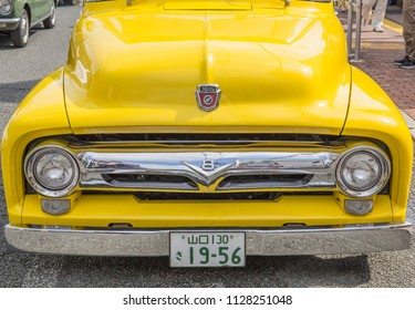 YAMAGUCHI, JAPAN - APRIL 8, 2018: A close up, front view of a bright yellow vintage Ford truck with a shiny, classic chrome bumper.