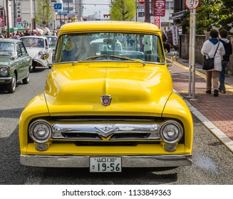 YAMAGUCHI, JAPAN - APRIL 8, 2018: The proud owner of a bright yellow vintage Ford truck with a shiny chrome bumper participates in a classic car festival parade.