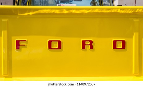 YAMAGUCHI, JAPAN - APRIL 8, 2018: A close up of the back of a bright yellow, classic Ford pickup truck with the Ford name in large bright red letters.