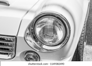 YAMAGUCHI, JAPAN - APRIL 8, 2018: A close up, black and white photo of the distinctive headlight of a classic Nissan Datsun Fairlady sports car.