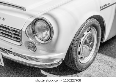 YAMAGUCHI, JAPAN - APRIL 8, 2018: A close up, black and white photo of the classic headlight of a Nissan Datsun Fairlady convertible sports car.