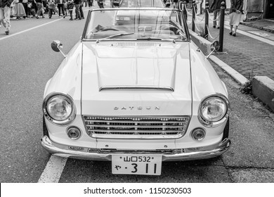 YAMAGUCHI, JAPAN - APRIL 8, 2018: A front view, black and white photo of a classic Nissan Datsun Fairlady convertible sports car parked beside a city street.
