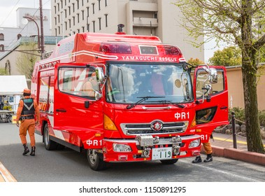 YAMAGUCHI, JAPAN - APRIL 8, 2018: Japanese firemen in orange uniforms get out of a large red firetruck on a city street.