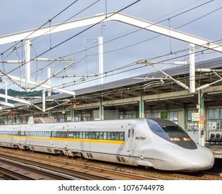 YAMAGUCHI, JAPAN - AUGUST 18, 2012: A white, aerodynamic, futuristic high speed train ('shinkansen') from Tokyo speeds by on its way across Japan.