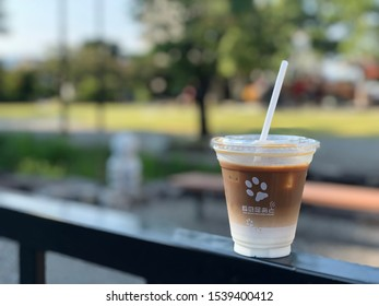 """YAMAGUCHI/JAPAN-Sep 26, 2019: A glass of iced latte, with the logo of a cafe called """"Kitsune no ashiato"""".  It is placed on metal bar in a public park."""