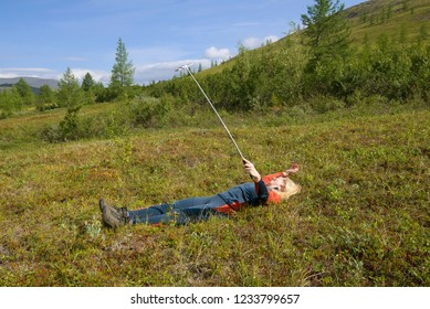 YAMAL, RUSSIA - AUGUST 20, 2018: A tourist girl lying on a mountainside takes a selfie. Polar Ural