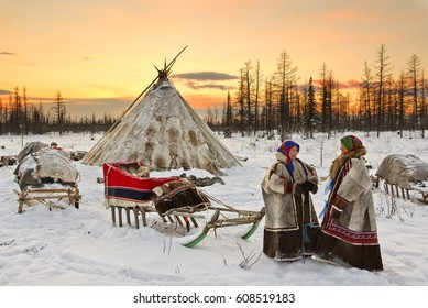 Yamal, Russia - February 15, 2017: Women of Nenets nationality stay near their yurts and sled. Nomad Nenets people live in yurts whole year, migrate with reindeer herd in tundra around polar circle.