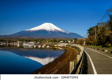 Yamanaka lake shore and village with mount Fujisan and skyline reflection on water against blue sky. Here is 1 of 5 Mt. Fuji lakes.