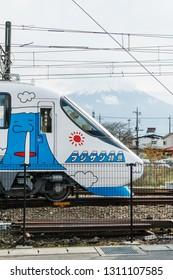 YAMANASHI, JAPAN - NOVEMBER 12, 2018: Day scene of Fujikyu express train with Fujisan graphic at Kawaguchiko station with Fujisan on the background at Kawaguchiko, Yamanashi, Japan