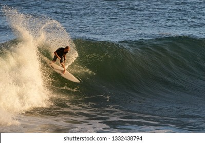 Yamba, NSW / Australia - February 12 2019: A skilled surfer 'smacks the lip' of a wave, as he performs a backside re-entry; the cut back produces a rooster tail; near the break wall at Turners Beach.