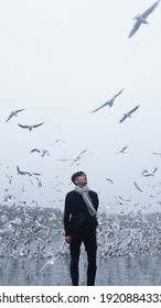Yamuna Ghat, New Delhi, India - 01-15-2020 : men surrounded by birds at the river