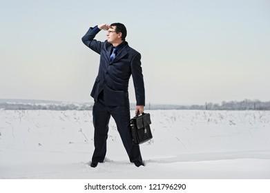 Yang businessman dressed in suit looks lost in snow desert.